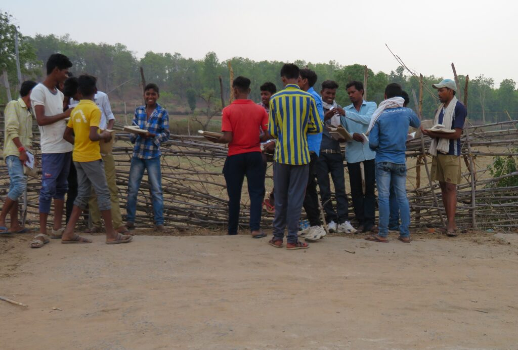 Teenage boys from Dobha village in Bandhavgarh, chatting whilst standing by a fence overlooking a farm, are holding their Tigers4Ever education packs